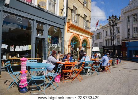 FOLKESTONE, UK - JUN 3, 2013: Customers dining at a sidewalk cafe on a sunny summer day