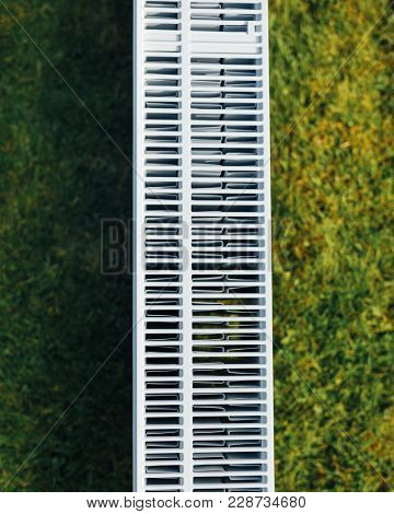 radiator mesh, green lawn background, ecological heating concept