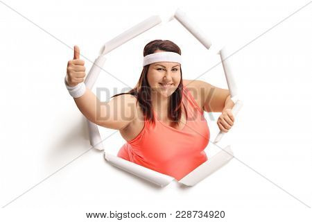 Overweight woman breaking through paper and making a thumb up gesture