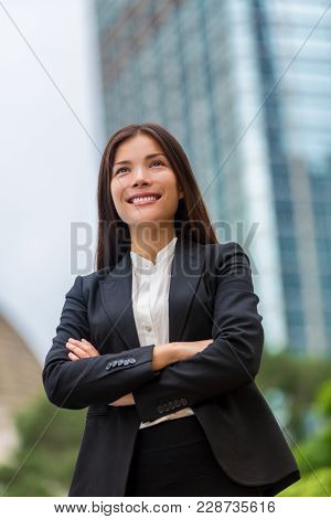 Asian businesswoman confident in Hong Kong. Businesswoman standing outdoor with city urban background in suit cross-armed. Young multiracial Chinese Asian / Caucasian professional in Hong Kong.