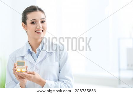 Female doctor holding contact lens case indoors