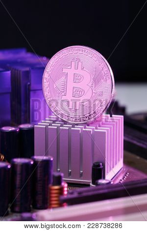 Photo of bitcoin and processor on pink background
