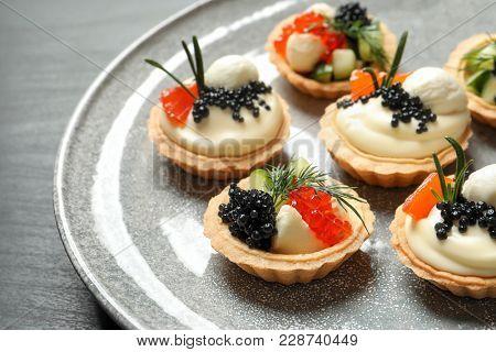 Tasty black caviar appetizers on plate