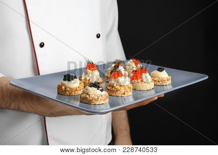 Man holding plate with caviar appetizers on black background