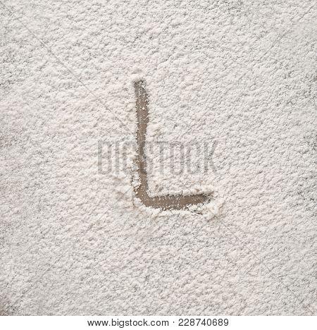 Letter L written on flour