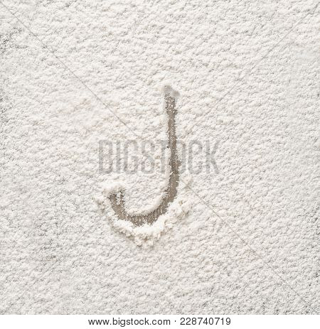 Letter J written on flour