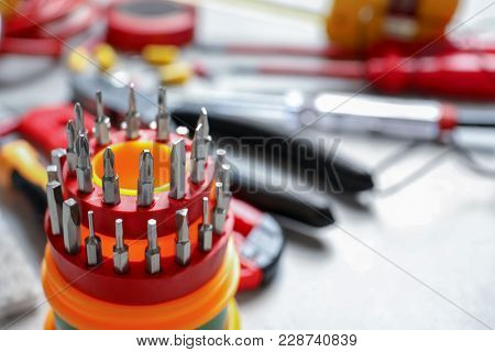 Screwdriver bit set and blurred electrical tools on background