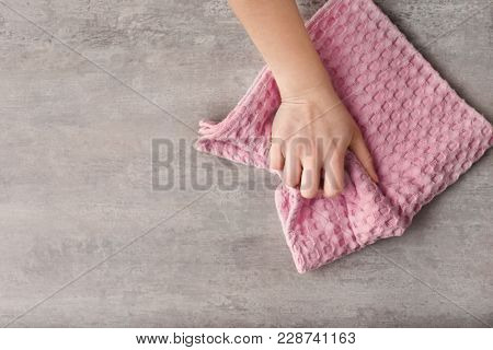 Woman wiping table with kitchen towel