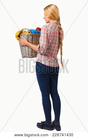 Back view of woman with  basket of dirty laundry. girl is engaged in washing. Rear view people collection.  Isolated over white background. Girl with very long hair holds up a laundry basket.