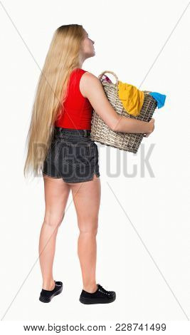 Back view of woman with  basket of dirty laundry. girl is engaged in washing. Rear view people collection.   Isolated over white background. Girl in shorts carries washing dirty clothes.
