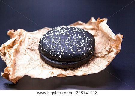 Bun for a black hamburger. A black bun with sesame on paper.