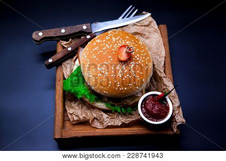 A juicy burger. Burger with marble beef, fork with knife and chili sauce