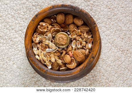 Walnut on brass in vintage wooden nut bowl with cracked walnut and peanut shells