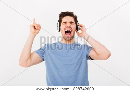 Portrait of happy man having short dark hair screaming his favorite song while listening to music via earphones with closed eyes isolated over white background