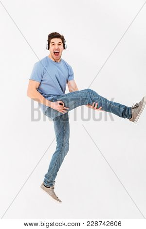 Full-length photo of rock star guy listening to music via headphones and holding leg like playing guitar isolated over white background