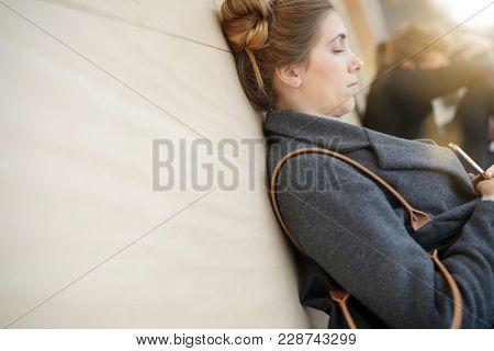 Student girl in school corridor resting with eyes shut