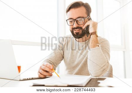 Successful man in eyeglasses running business from home workplace speaking on smartphone and writing down notes on paper