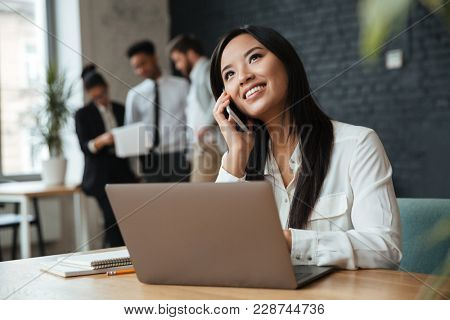 Image of happy young asian business woman sitting indoors using laptop computer. Looking aside talking by mobile phone.