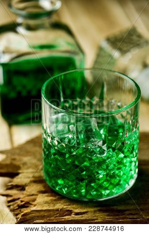 closeup of a glass with dyed green whiskey on a wooden rustic surface and a liquor bottle with dyed green whiskey in the background