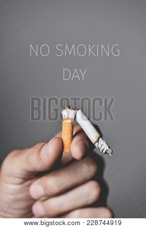 closeup of a young caucasian man with a broken lit cigarette in his hand and the text no smoking day