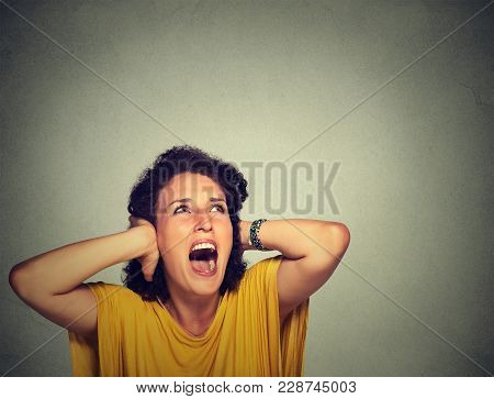 Young Annoyed Unhappy Stressed Woman Covering Her Ears, Looking Up, Screaming Stop Making Loud Noise