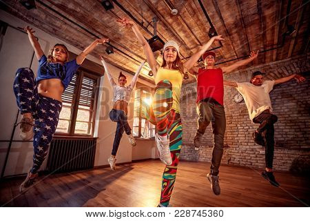 Young modern dancing group practice dancing in jump. Sport, dancing and urban culture concept