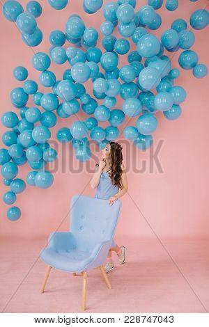 Little Girl In Blue Dress In A Pink Room