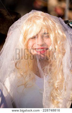 Pernik, Bulgaria - January 26, 2018: Man Dressed As Bride Laughs Loudly Under Transparent White Veil