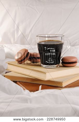 Morning Cup Of Coffee With Chocolate Cakes Macaroons, On A Pile Of Books In Bed. The Inscription On