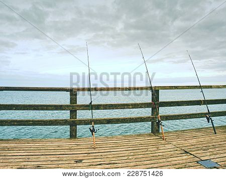 Fishers Rods Against Handrail Of Wooden Bridge.  Fishing On Harbor Mole. Overcast Day, With The Hidd