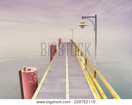 Empty Steel Mole In Harbor. Steel Grate Board. Black Cormorant Sit On Pole. Autumn Mist On Pier Abov
