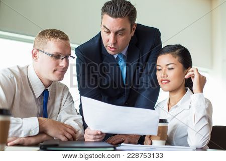 Portrait Of Confident Business Team, Caucasian Mid Adult Executive, Young Man And Asian Woman, Discu