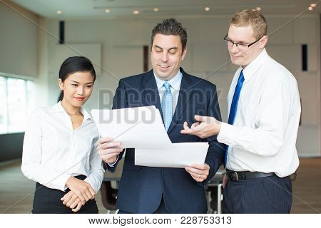 Portrait Of Happy Mid Adult Executive Reading Reports Of His Young Employees, Caucasian Man And Asia