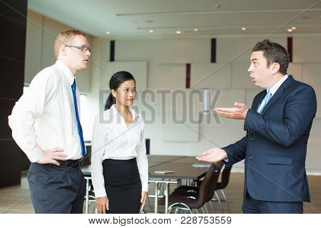Irritated Mid Adult Caucasian Executive Scolding Young Employees, Man And Asian Woman, For Bad Resul