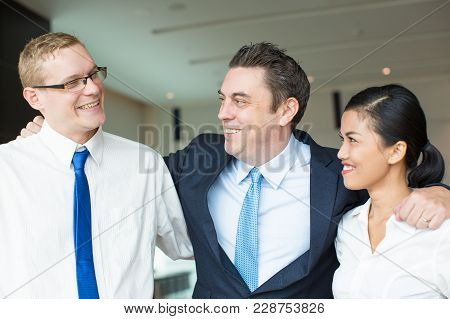 Portrait Of Happy Mid Adult Executive Embracing His Workers, Young Caucasian Man And Asian Woman And