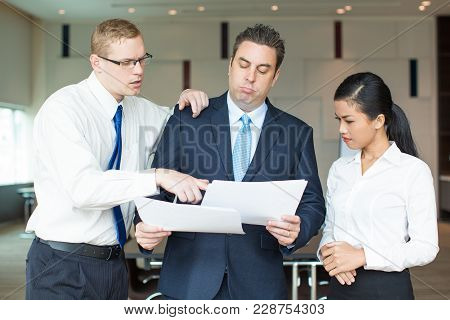 Portrait Of Skeptical Mid Adult Boss Reading Reports Of Young Workers, Caucasian Man And Asian Woman