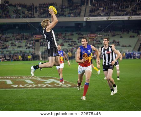 MELBOURNE - AUGUST 20 : Collingwood's  Dale Thomas takes a mark during their win over Brisbane - August 20, 2011 in Melbourne, Australia.