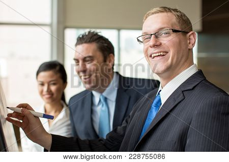 Closeup Of Smiling Business Leader In Suit Drawing On Flipchart For His Two Colleagues. Business Gro