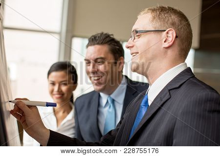 Closeup Of Smiling Businessman In Glasses Drawing On Flipchart For His Two Colleagues. Business Team