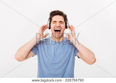 Portrait of attractive guy having short dark hair screaming his favorite song while enjoying music via earphones with closed eyes isolated over white background