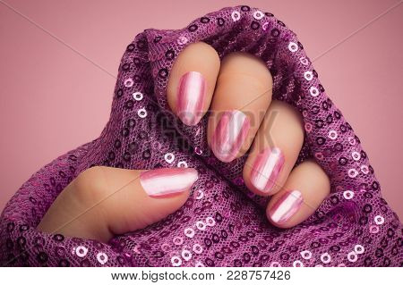 Female Hand With Shiny Bright Pink Lacquered Nails Is In Purple Textile Material With Glitters On Pi