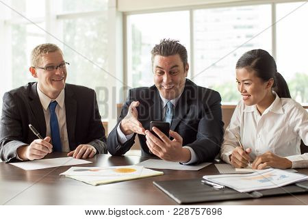 Three Smiling Business People Using Mobile Phone At Conference Table With Reports. Business Team Hav