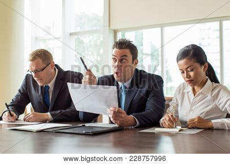 Serious Asian Woman And Caucasian Man In Glasses Writing Notes While Their Male Coworker In Suit Hol
