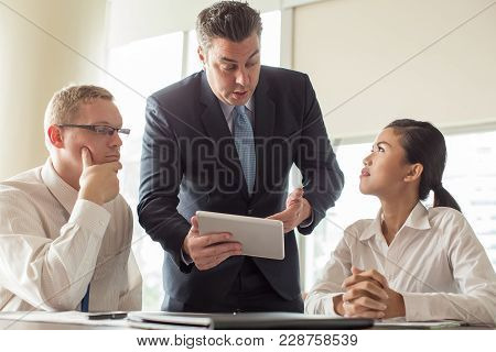 Middle Aged Businessman In Suit Pointing At Tablet And Talking To Young Colleagues. Boss Giving Task