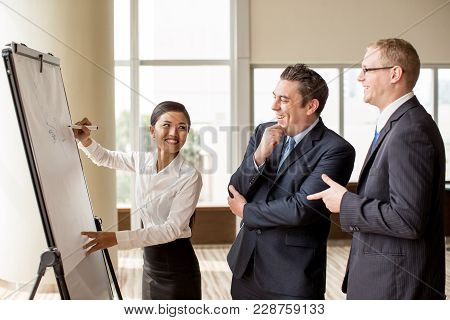 Young Smiling Asian Business Lady Drawing On Flipchart For Two Laughing Colleagues. Creative Busines