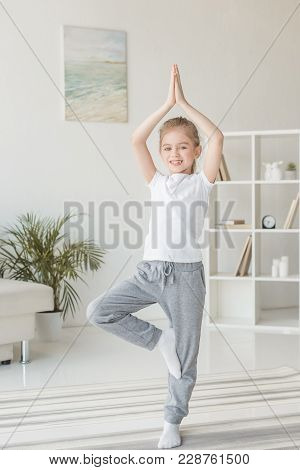 Beautiful Little Child Practicing Yoga In Tree Pose