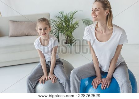 Happy Mother And Daughter Sitting On Fit Balls At Home