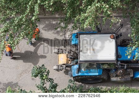 Road Repair. Asphalt Cutting Machine And Road Workers Top View