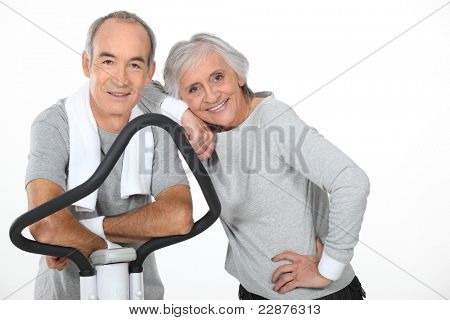 Senior couple using gym equipment
