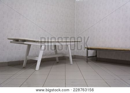 Wooden Massage Table And Bench On A White Tile Background